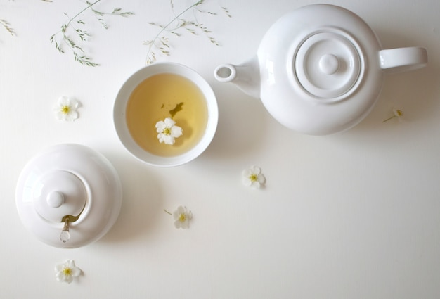 Conjunto com chá verde, xícaras e chaleiras, folhas de hortelã e flores de camomila, com espaço livre para texto, banner longo e largo
