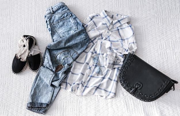 Conjunto com roupas da moda feminina, camisa, jeans e bolsa. olhar da moda na moda. postura plana.