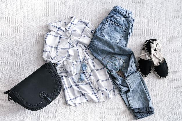 Conjunto com roupas femininas da moda, camisa, jeans e bolsa com acessórios.