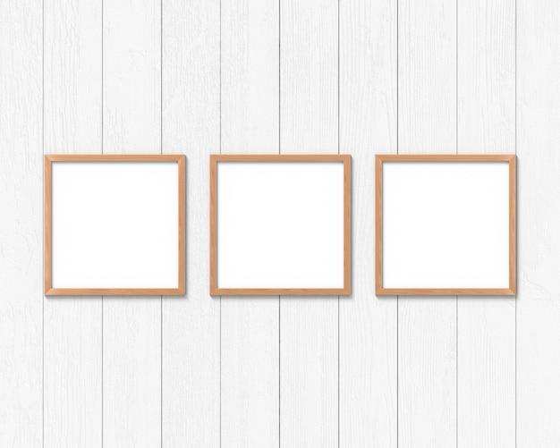 Conjunto de 3 maquete de molduras quadradas de madeira pendurado na parede. base vazia para imagem ou texto. renderização em 3d.