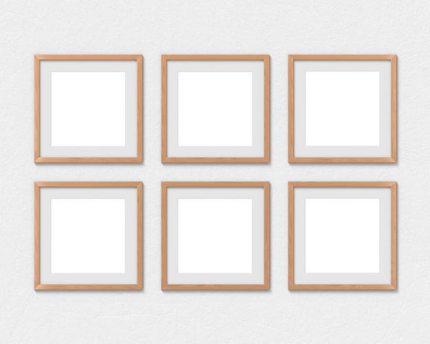Conjunto de 6 molduras quadradas de madeira com uma borda pendurada na parede. renderização em 3d.