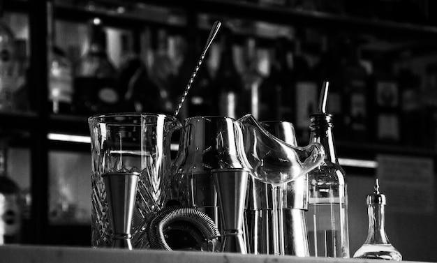 Conjunto de acessórios de bar para fazer coquetéis, localizado no bar, atrás está uma estante com licores e álcool forte. mídia mista