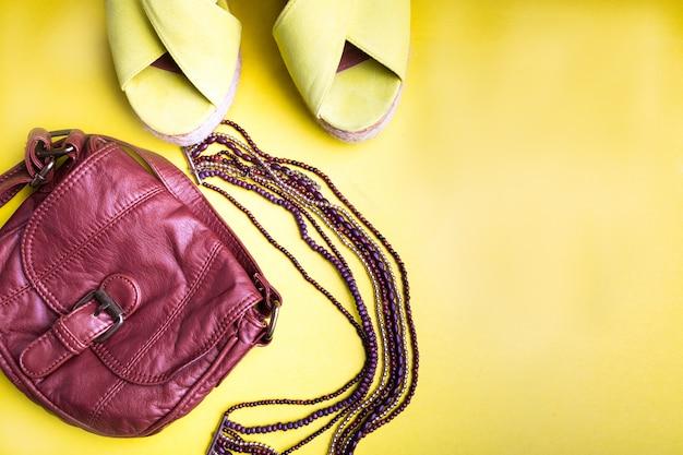 Conjunto de acessórios de coisas de mulher para a temporada de verão. brown bag sandálias com plataforma amarela, colar. configuração plana.