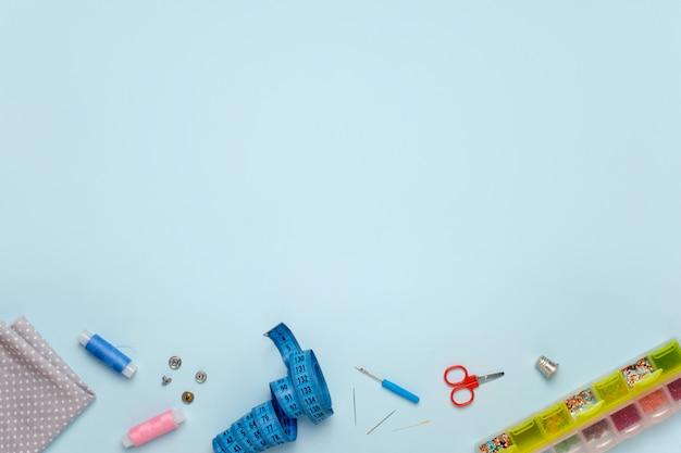 Conjunto de acessórios de costura em um fundo azul, vista superior