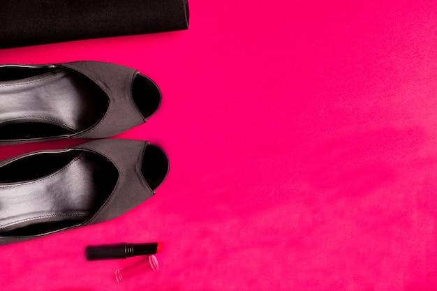 Conjunto de acessórios de moda senhora. preto e rosa. mínimo. sapatos pretos, batom e bolsa rosa. postura plana.