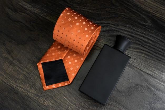 Conjunto de acessórios masculinos, relógios, gravata, perfumes em um fundo escuro de madeira.