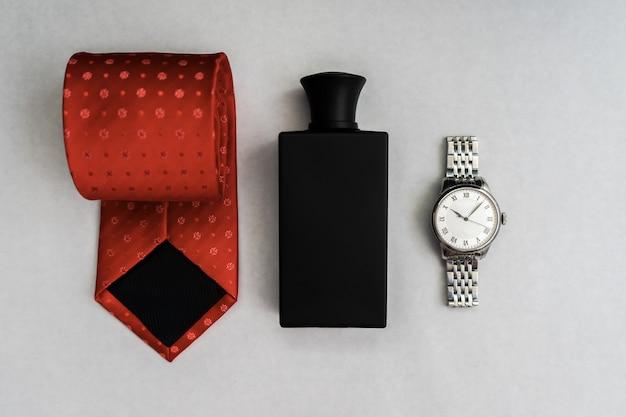 Conjunto de acessórios masculinos, relógios, gravata, perfumes, sobre um fundo claro.