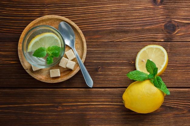 Conjunto de açúcar mascavo e fatia de limão em uma placa de madeira e limão e folhas em uma mesa de madeira
