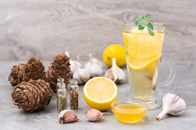 Conjunto de agentes antivirais naturais: limão, alho, mel, ervas, resina de cedro em cima da mesa. medicina alternativa. cuidados de imunidade