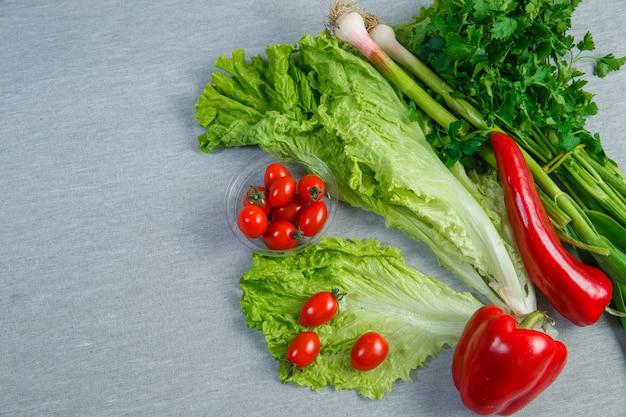 Conjunto de alface, verduras, pimentas e tomate cereja em um pires em cinza. vista do topo.