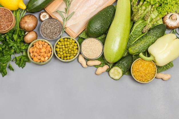 Conjunto de alimentos balanceados, vegetais verdes, sementes nozes, carne de frango em fundo cinza