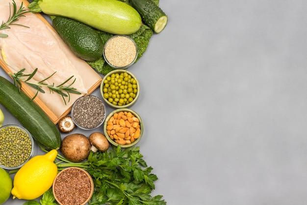 Conjunto de alimentos equilibrados, vegetais verdes, sementes nozes, carne de frango.