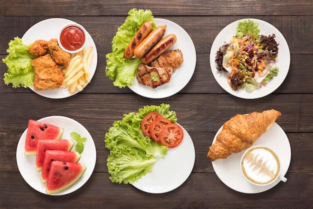 Conjunto de alimentos frango frito e batatas fritas, carne e linguiça para churrasco, salada, melancia, prato vazio e café no fundo de madeira