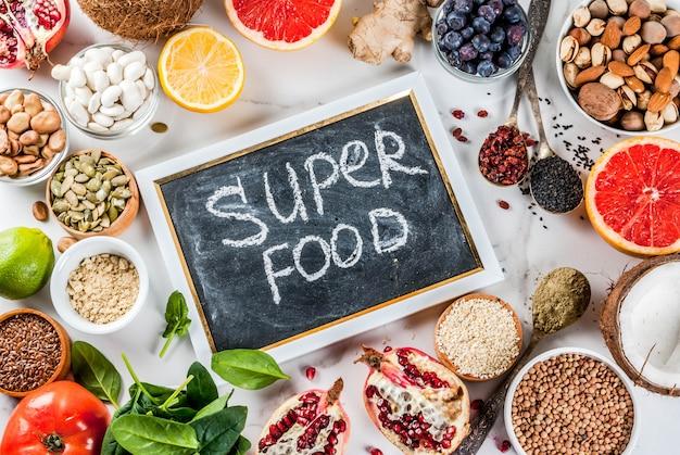 Conjunto de alimentos orgânicos dieta saudável, superalimentos feijão, legumes, nozes, sementes, verduras, frutas e legumes ... branco. quadro de vista superior