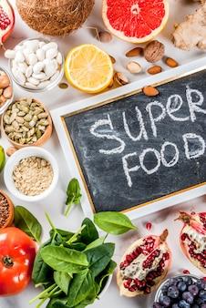 Conjunto de alimentos orgânicos dieta saudável, superalimentos - feijão, legumes, nozes, sementes, verduras, frutas e legumes ... espaço branco cópia de fundo. vista do topo