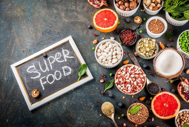 Conjunto de alimentos orgânicos dieta saudável, superalimentos - feijão, legumes, nozes, sementes, verduras, frutas e legumes. fundo azul escuro cópia espaço vista superior