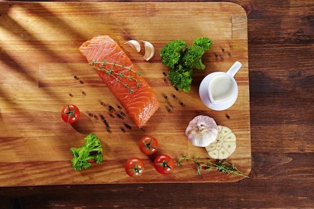Conjunto de alimentos saudáveis anticâncer na mesa de madeira. peixe salmão vermelho, brócolis, alho, leite, pimenta e tomate espalhados por uma mesa. conceito de refeição saudável, vista superior