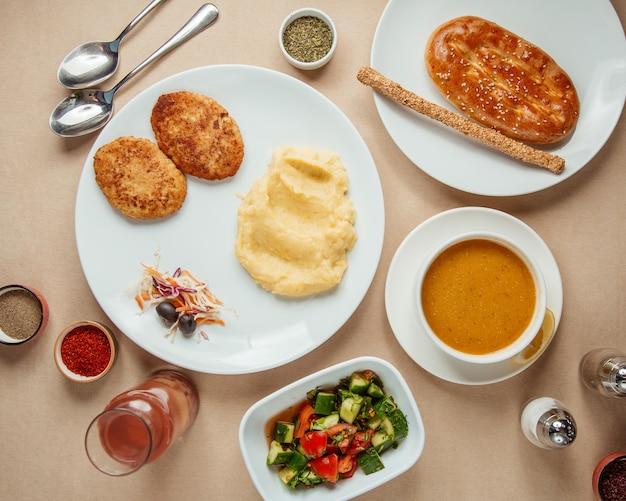 Conjunto de almoço costeletas de sopa de lentilha com salada de choban com compota de batata morna vista superior