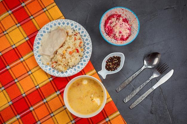 Conjunto de almoço delicioso na mesa cinza coberto com toalha laranja. o almoço contém sopa, arroz e frango e salat de beterraba.