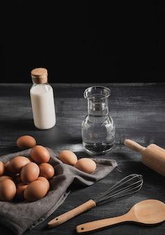 Conjunto de alto ângulo de utensílios de cozinha ao lado de ovos