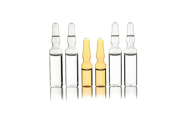 Conjunto de ampolas de vidro transparente com líquido em um branco