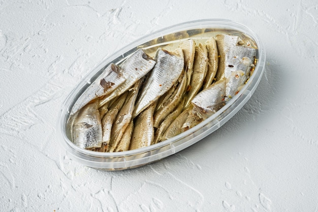 Conjunto de anchova em conserva, em recipiente de plástico, sobre fundo branco