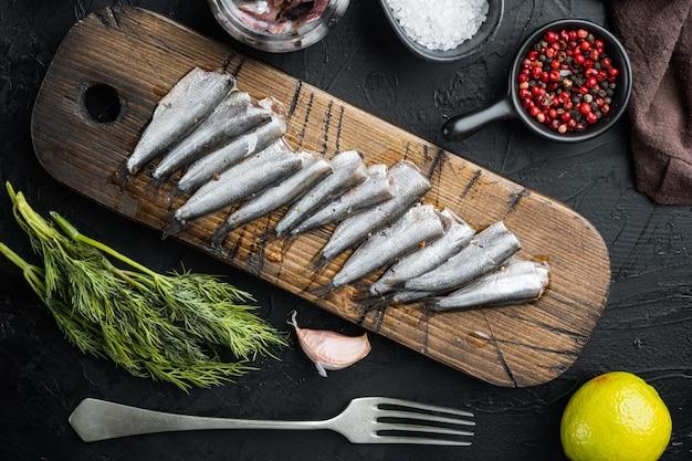 Conjunto de anchova em conserva, em uma tábua de madeira, em fundo preto com ervas e ingredientes, vista de cima plana lay
