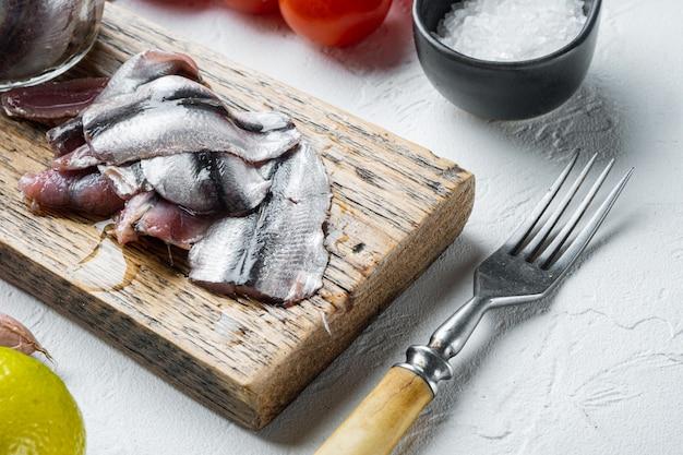 Conjunto de anchova em conserva, numa tábua de madeira, em fundo branco com ervas e ingredientes