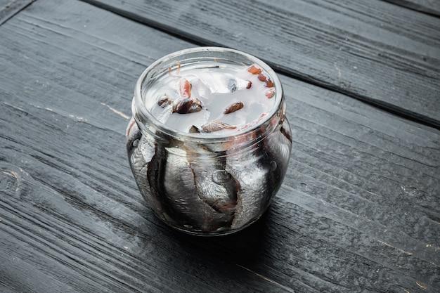 Conjunto de anchova em lata, em frasco de vidro, sobre mesa de madeira preta