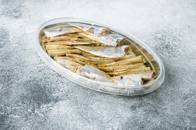 Conjunto de anchovas em lata, em recipiente de plástico, em fundo cinza, vista de cima plana, com espaço para texto e copyspace
