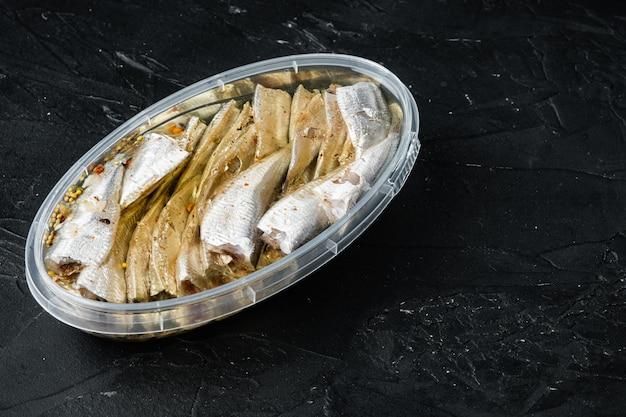 Conjunto de anchovas em lata, em recipiente de plástico, em preto