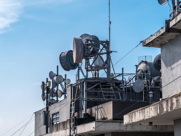 Conjunto de antenas de comunicação no telhado de um edifício.
