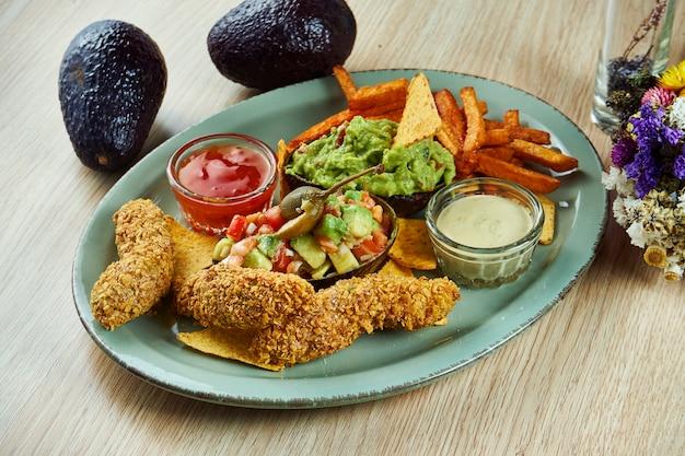 Conjunto de aperitivos de abacate. frito varas de abacate em panados crocantes. guacamole e nachos. abacate recheado com alcaparras e tomates. batata-doce com molhos em um prato. ótimo almoço