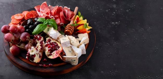 Conjunto de aperitivos para vinho, jamon, calabresa, queijo, uvas, pêssego e azeitonas em uma placa de madeira.