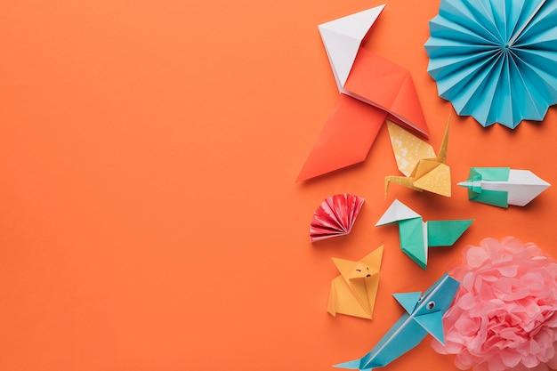 Conjunto de artesanato de arte de papel origami na superfície laranja brilhante