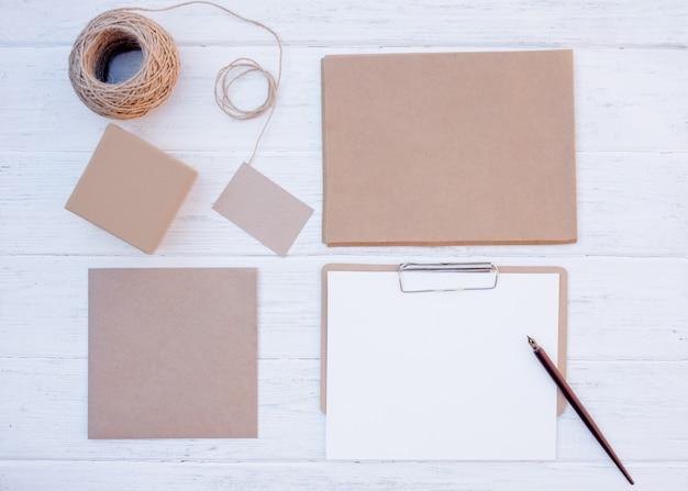 Conjunto de artesanato de itens diferentes vazios, caixas de presente, envelopes, cartão, folha, corda em fundo de madeira