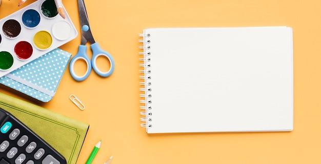 Conjunto de artigos de papelaria ao lado do bloco de desenho