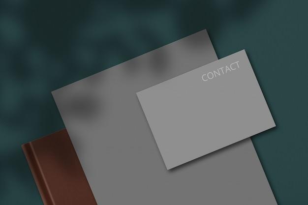 Conjunto de artigos de papelaria com o bloco de notas cinza em branco vazio e cartão de visita para seu contato