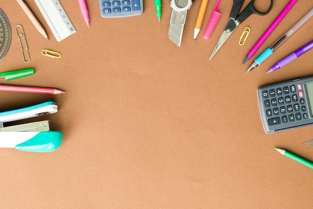 Conjunto de artigos de papelaria na mesa marrom, vista superior. conceito de escola