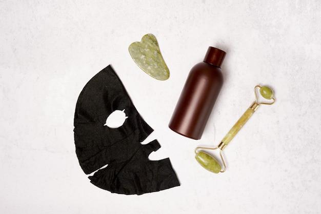 Conjunto de autocuidado. rolo facial, raspador de guasha massageador, frasco de óleo cosmético e máscara facial. postura plana