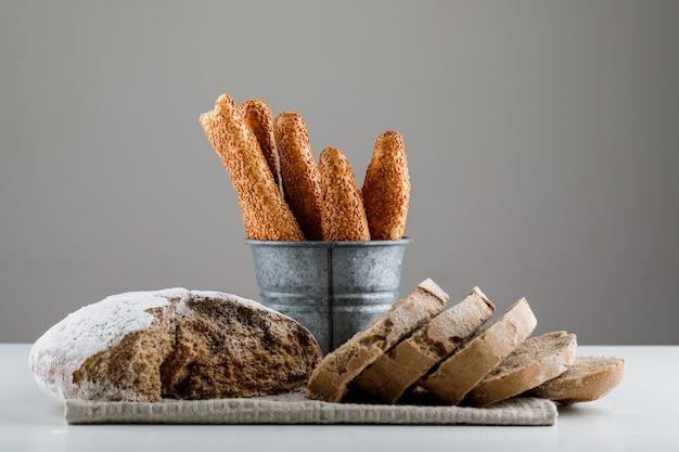 Conjunto de bagel turco e pão fatiado em uma superfície branca e cinza. vista lateral.
