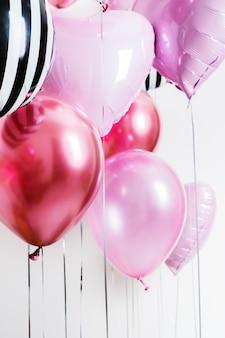 Conjunto de balões em forma de um coração e redondo rosa e listrado na luz de fundo com espaço de cópia.
