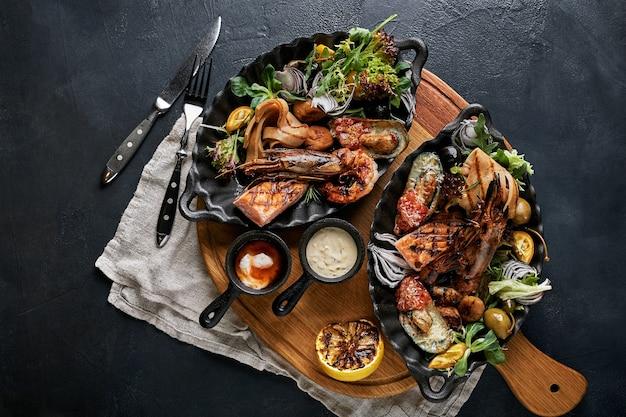 Conjunto de bandeja de frutos do mar assados mistos. contém camarões grelhados, lulas de calamari e pimenta de alho de peixe barracuda com molho picante de pimenta e batata, em tábua de madeira e fundo preto.