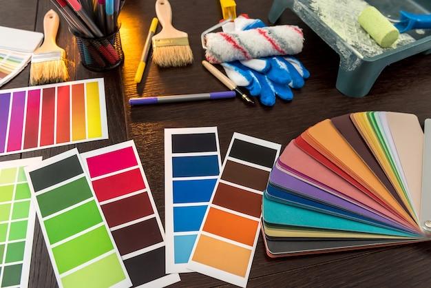 Conjunto de bandejas de rolos de pincéis e paleta de papel colorido na placa de madeira