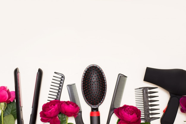Conjunto de barbeiro de diferentes escovas de cabelo e secador de cabelo com rosas rosa em fundo branco, com um espaço de cópia.