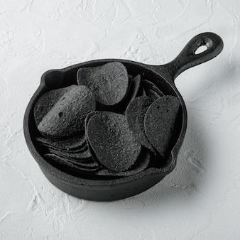 Conjunto de batata frita crocante preta, em frigideira de ferro fundido, em superfície de pedra branca, formato quadrado