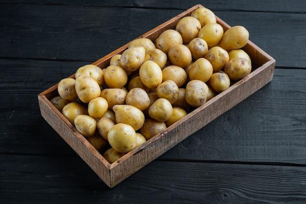 Conjunto de batatas brancas orgânicas para bebês, em caixa de madeira, na mesa de madeira preta