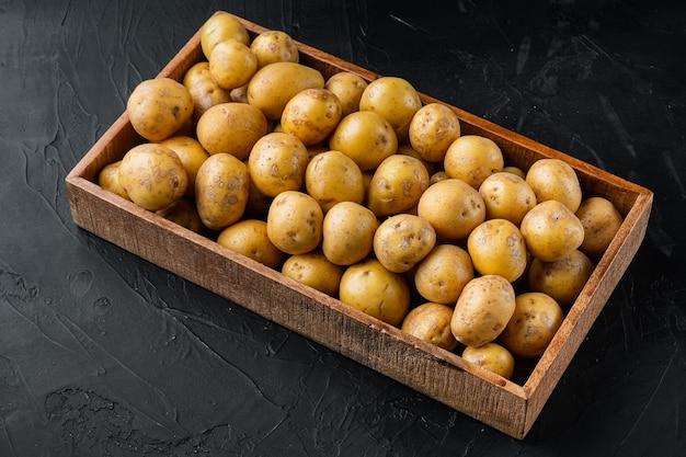 Conjunto de batatas brancas orgânicas para bebês, em caixa de madeira, sobre mesa de pedra preta