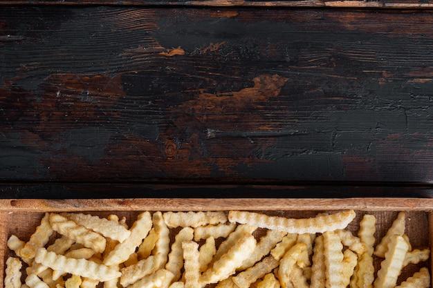 Conjunto de batatas fritas congeladas, em caixa de madeira, na velha mesa de madeira escura, vista de cima plana lay