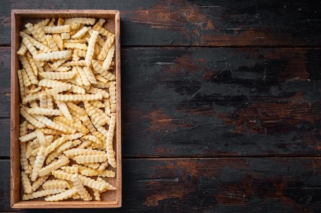 Conjunto de batatas fritas congeladas para forno amassado, em caixa de madeira, na velha mesa de madeira escura, vista de cima plana lay